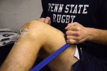 Senior Blaze Feury uses resistance bands to strengthen his knee on Nov. 8, 2013, two weeks after the Penn State rugby team captain tore his ACL. Feury, from Denville, N.J., goes to the East Area Locker Training Room every day to work with a trainer.