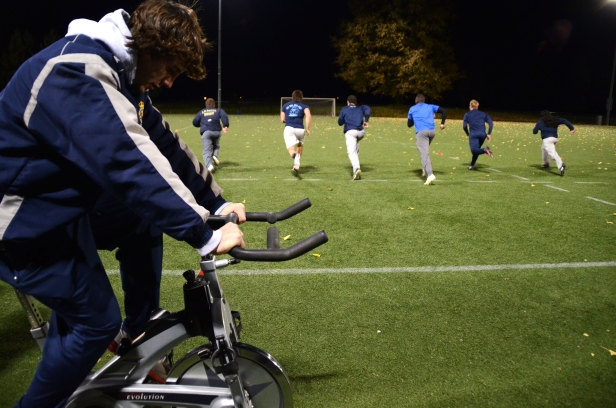 Feury exercises on the stationary bike while the rest of the rugby team runs suicides at conditioning practice on Nov. 12, 2013 at the fields behind Rec Hall. Even though Feury can't participate in practice, the captain has to attend every team practice.