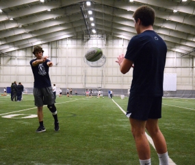 Feury plays catch with one of his teammates, who is also injured, at rugby practice in Holuba Hall on Dec. 4, 2013. The players who are injured are not allowed to participate in the practice, but are still required to go.